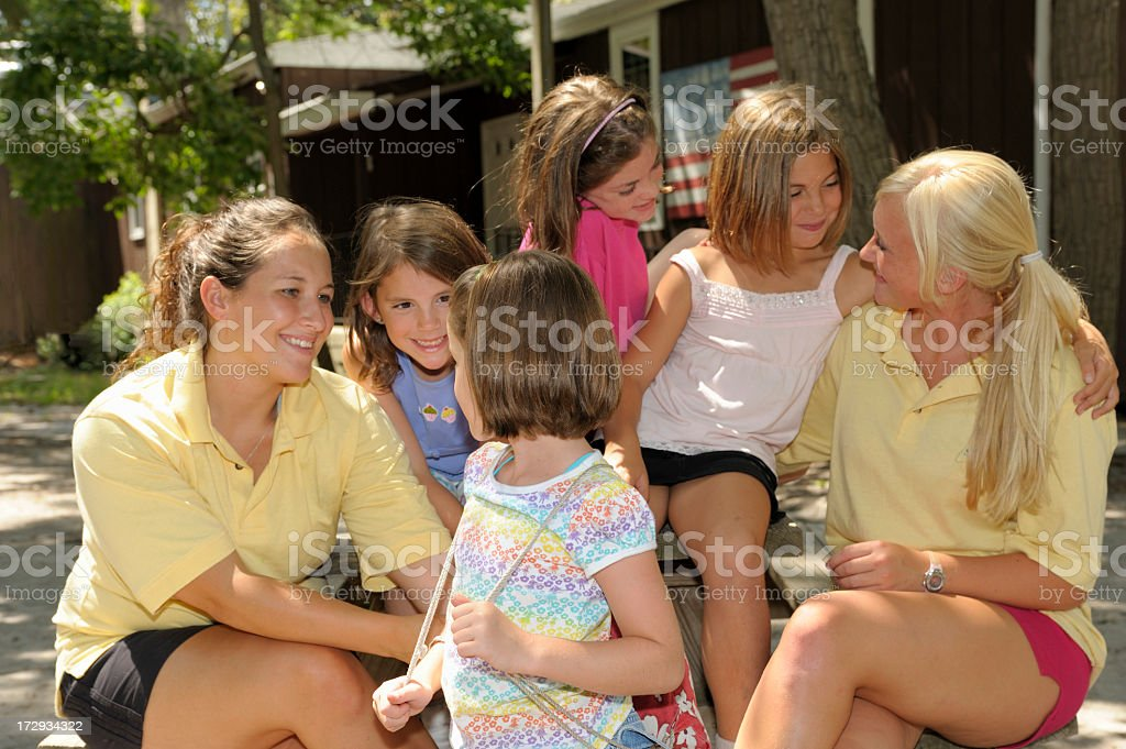 Two women with four young smiling girls outside royalty-free stock photo