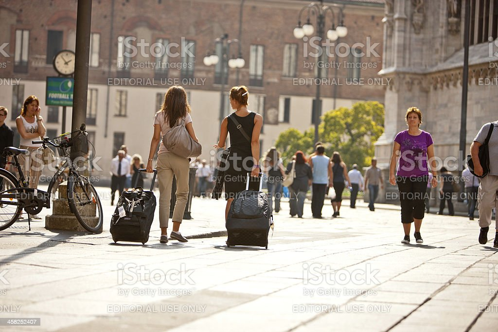 Two Women with luggage walking on Piazza del Duomo, Milan royalty-free stock photo