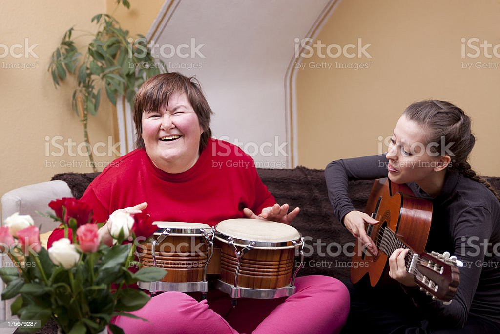 Two women with musical instruments having fun stock photo
