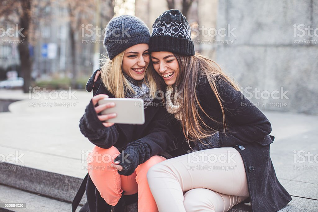 Two women with phone in the park stock photo