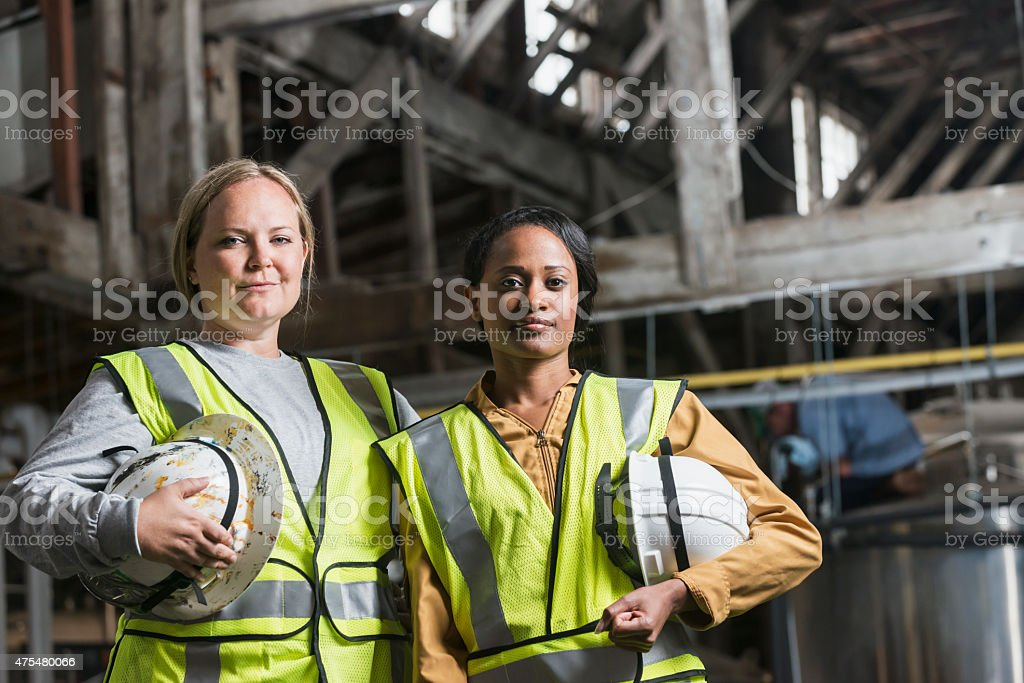 Two women with safety vests and hard hats in warehouse stock photo