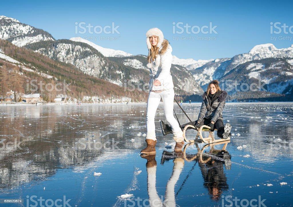 Two women with sled on frozen Lake Grundlsee, Austria stock photo