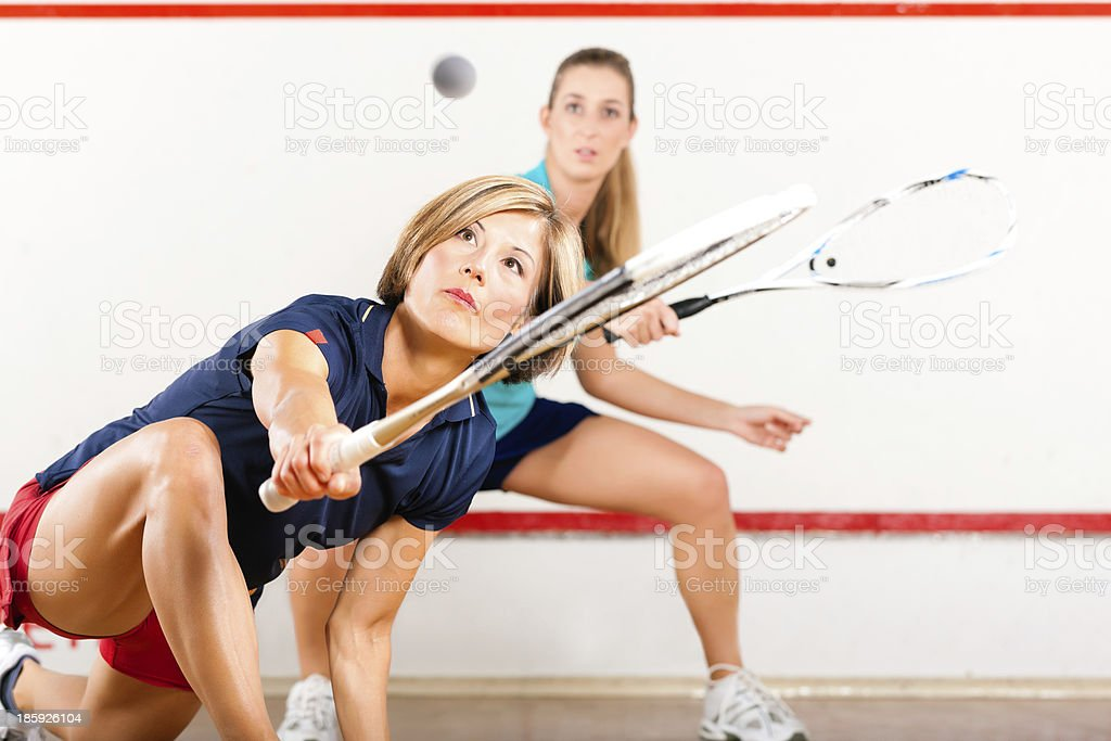 Two women with squash racquets playing together at a gym stock photo