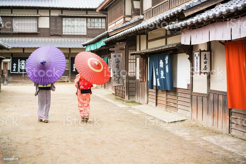 Two women with umbrellas walking on an old street, Japan stock photo