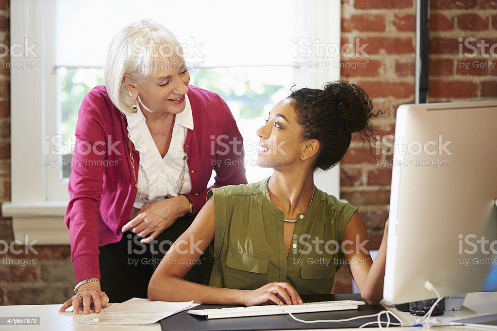 Two Women Working At Computer In Contemporary Office stock photo