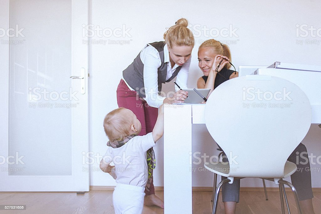Two women working at home while their baby plays around stock photo