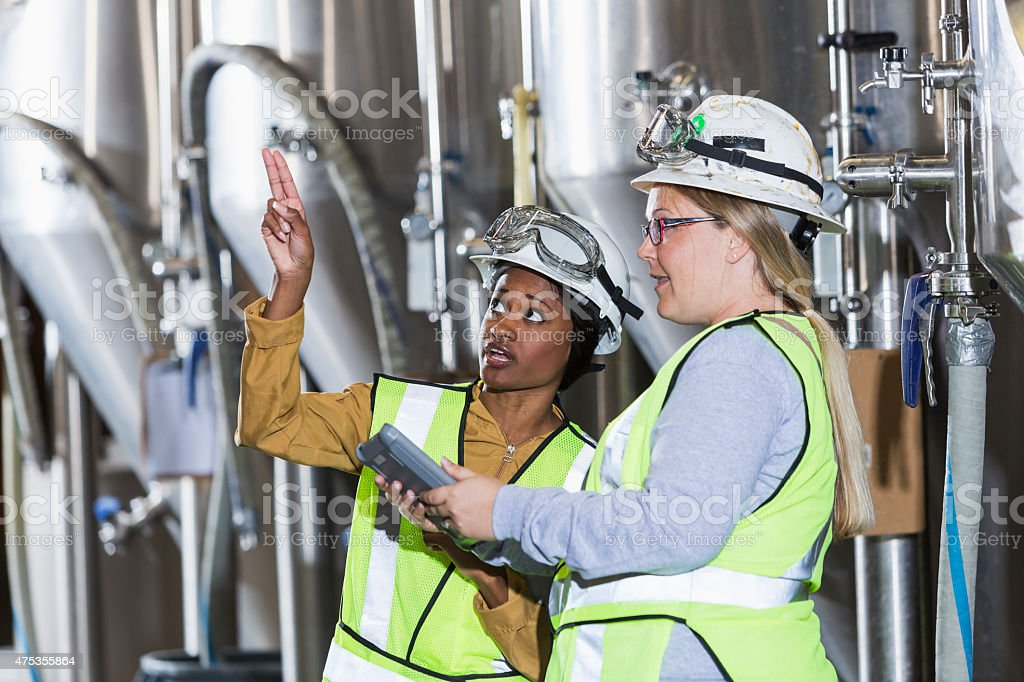 Two women working in a factory wearing hardhats stock photo