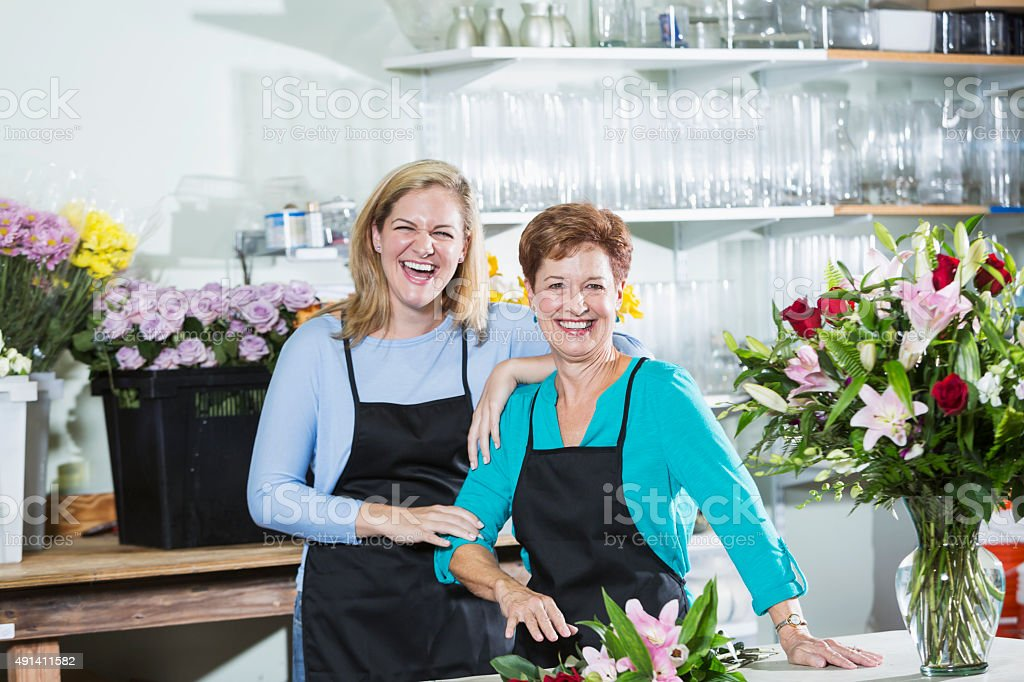 Two women working in a flower shop wearing aprons stock photo