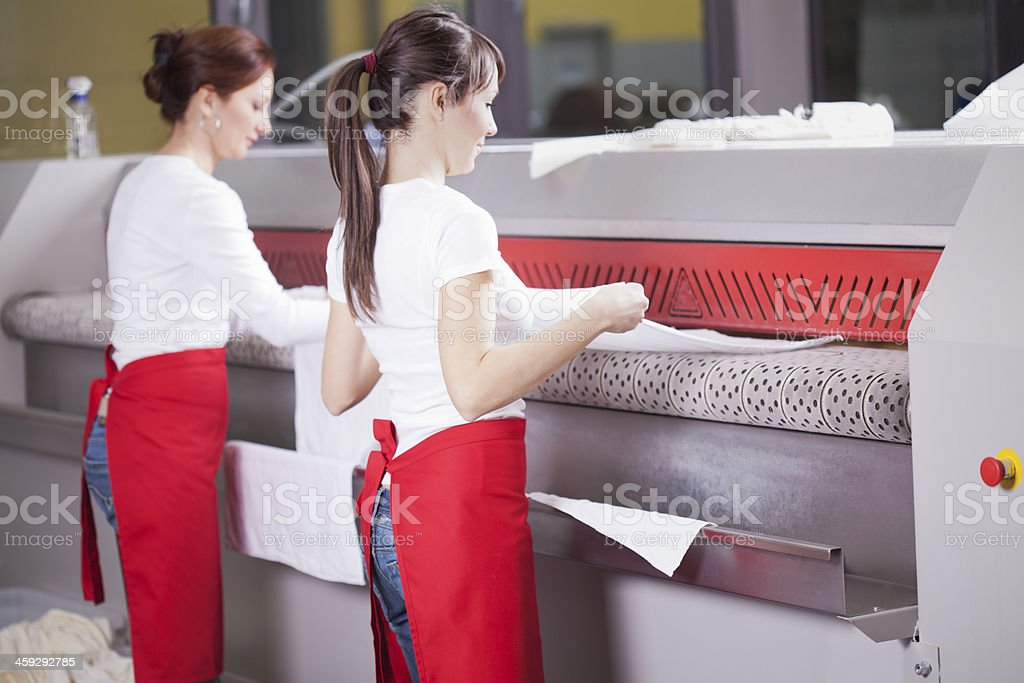 Two women working on an industrial ironing machine  stock photo