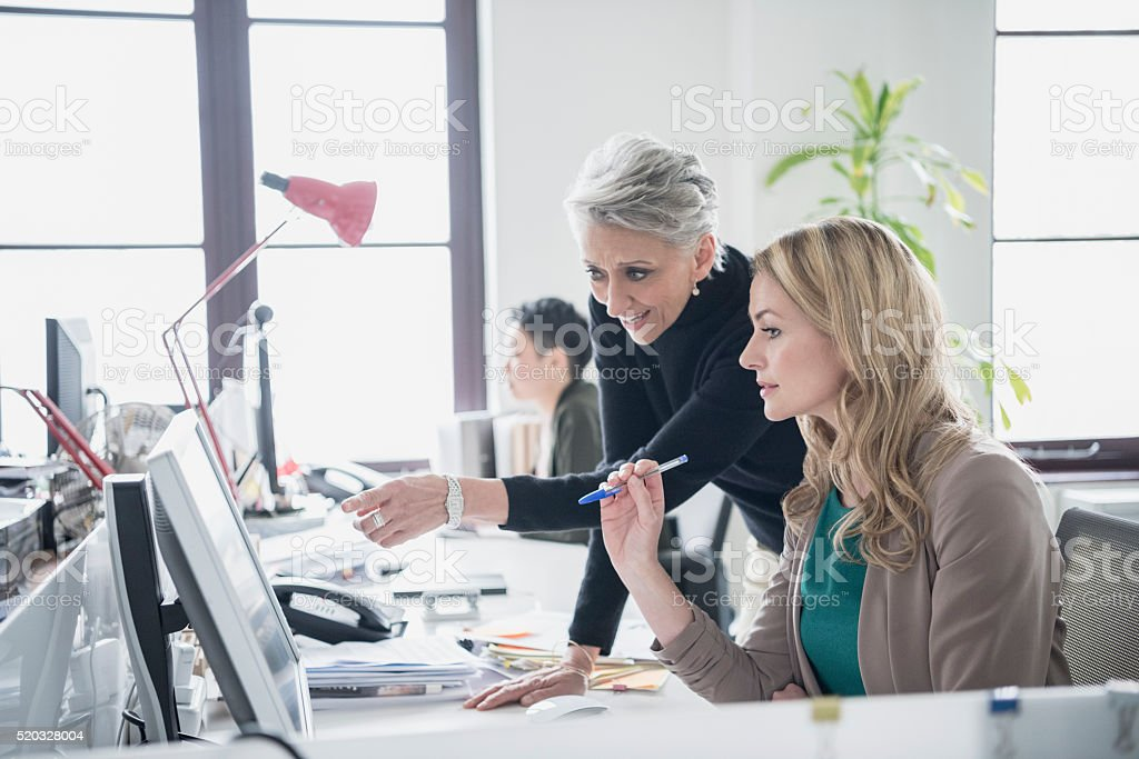 Two women working on computer in modern office stock photo