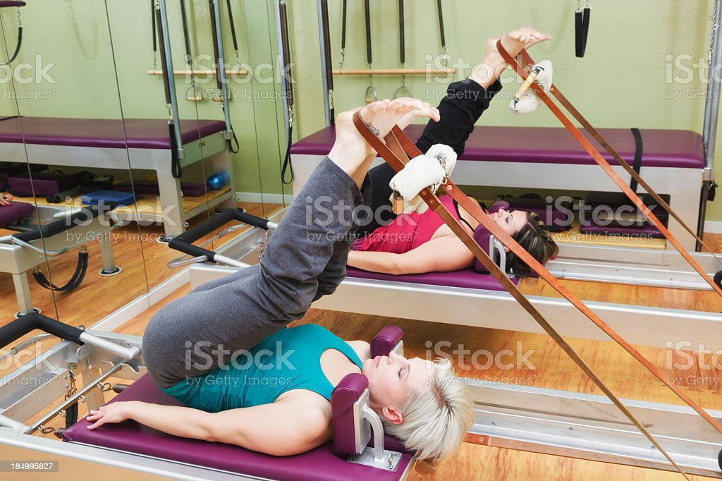 Two women working on Pilates reformer machines in a gym stock photo