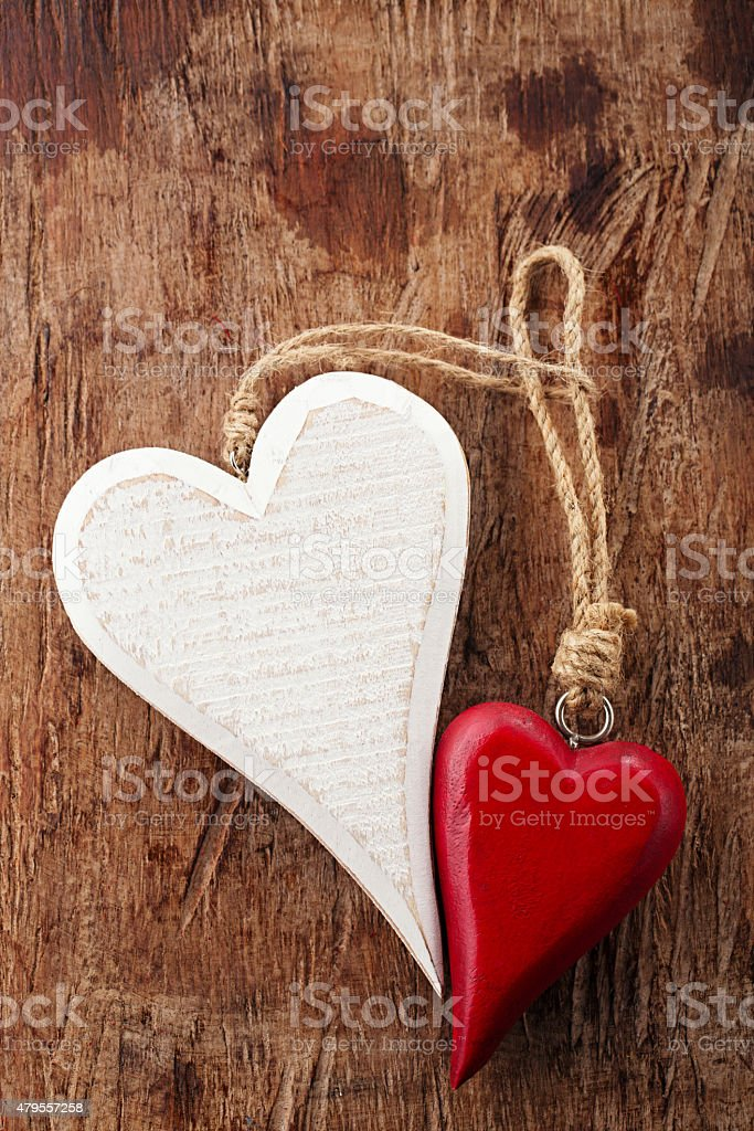 two wood hearts, red and white on old wooden background stock photo