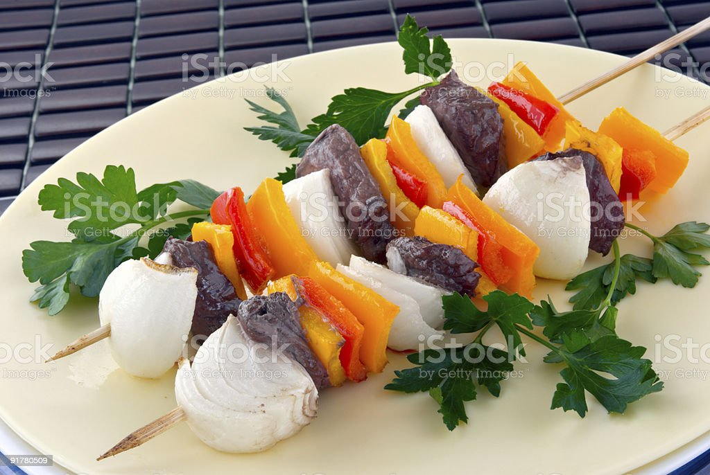 two wood skewers holding steak peppers and onion shish kebabs royalty-free stock photo