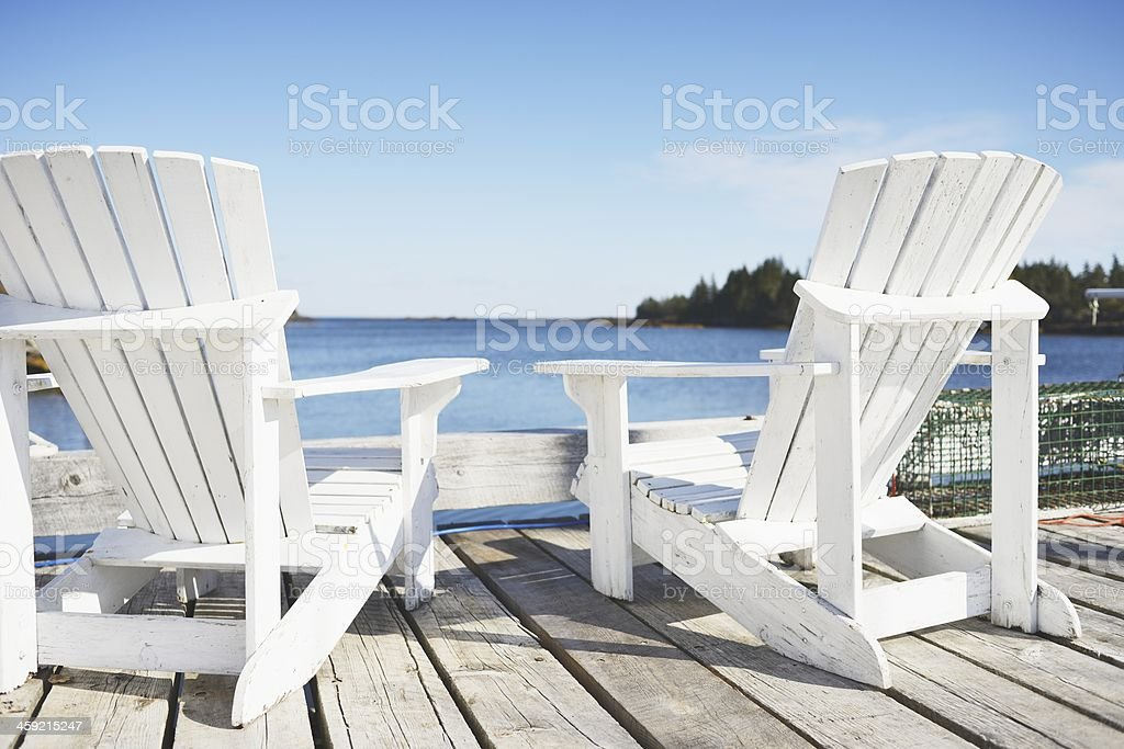 Two Wooden Adirondak Deck Chairs with Sea View stock photo