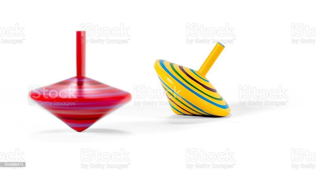 Two wooden and colorful spinning tops stock photo