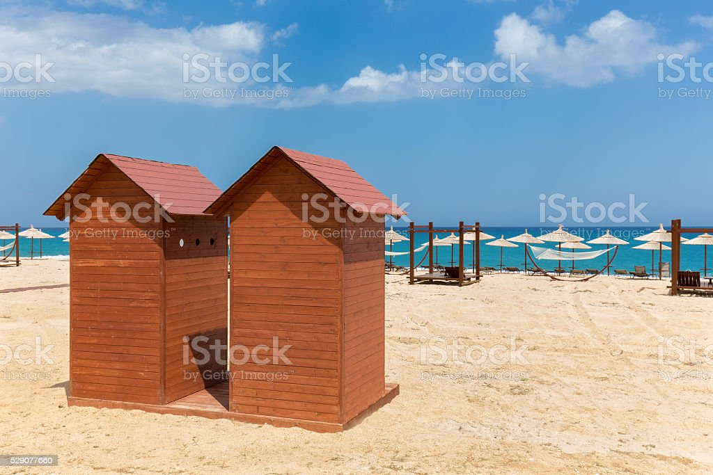 Two wooden beach cabins on greek sand coast stock photo