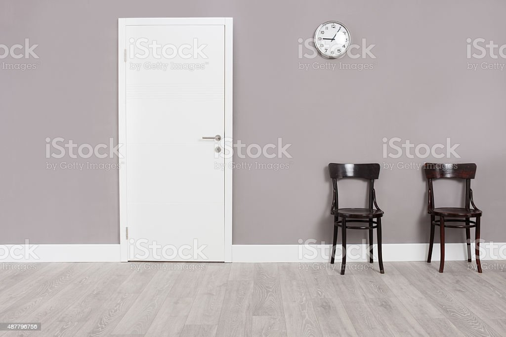 Two wooden chairs in a waiting room stock photo