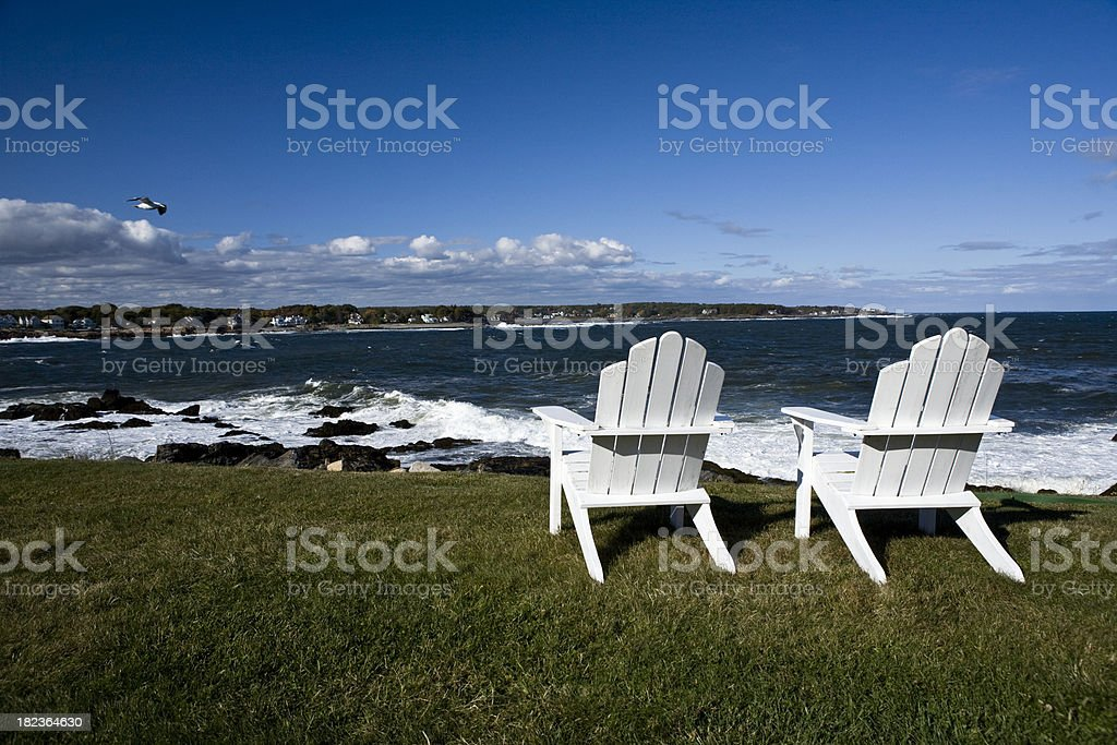 Two wooden chairs on sand next to the ocean royalty-free stock photo