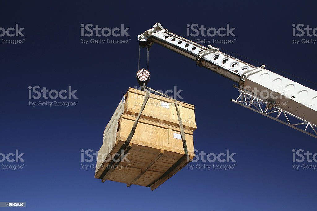 Two wooden crates hanging from a crane lift  stock photo