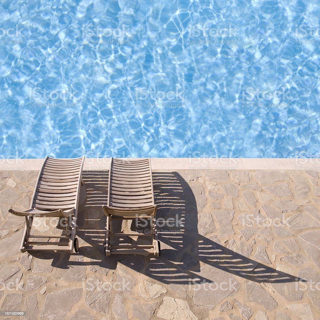 Two wooden deckchairs at the edge of a swimming pool stock photo