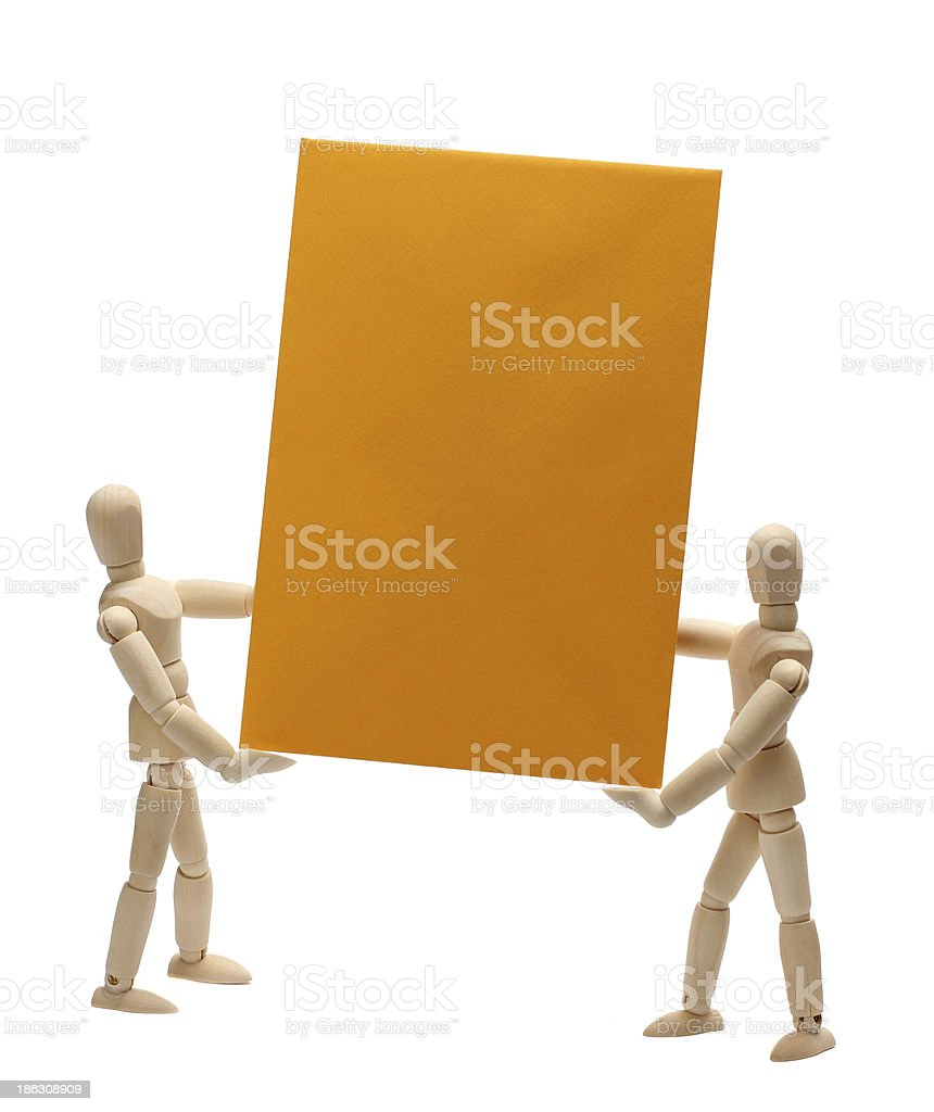 two wooden dolls holding yellow paper stock photo