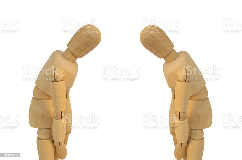 two wooden figure bow eachother concept stock photo