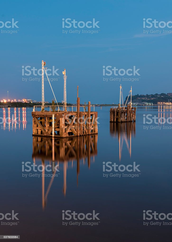 Two wooden jettys reflecting the calm water stock photo