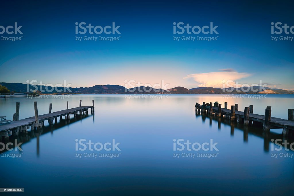 Two Wooden pier  jetty   blue lake sunset and sky refle stock photo