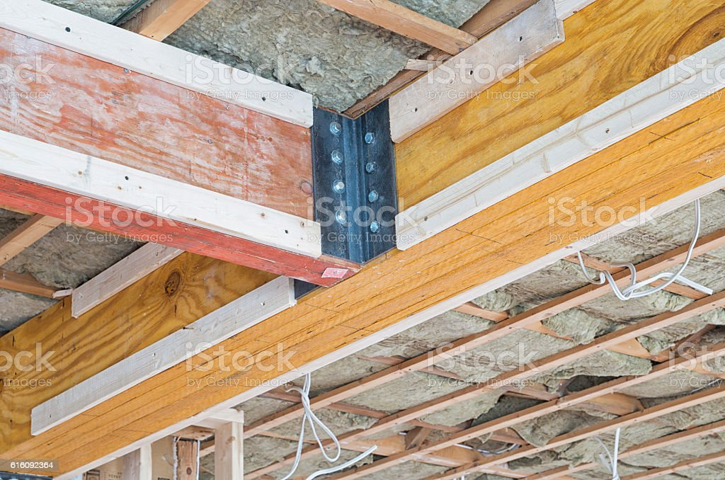 Two wooden supporting beams intersecting on ceiling of house stock photo