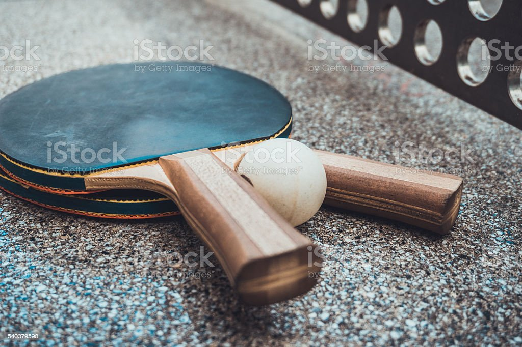 Two wooden table tennis bats with a ball stock photo