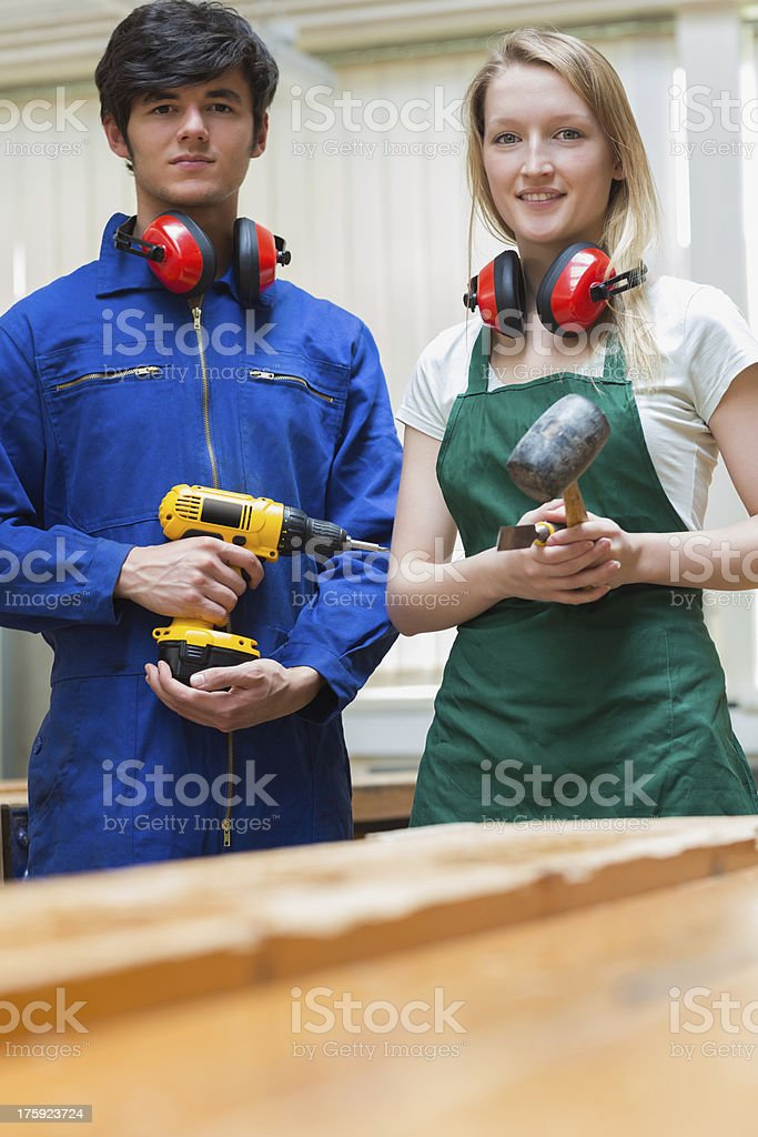 Two woodworking students standing before a workbench royalty-free stock photo