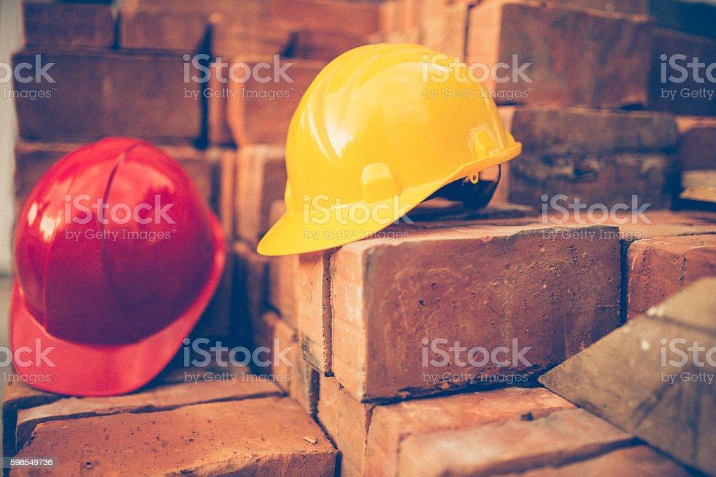 Two work helmets on bricks stock photo