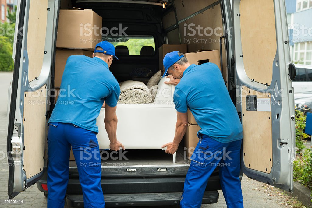Two Workers Adjusting Sofa In Truck stock photo