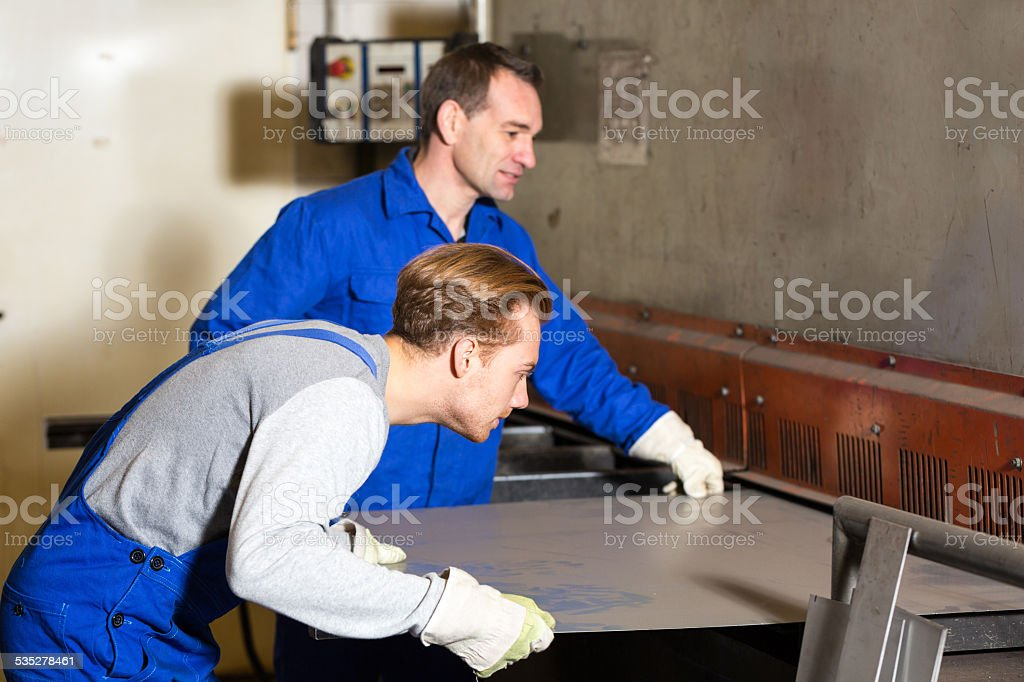 Two workers bending sheet metal with large machine stock photo
