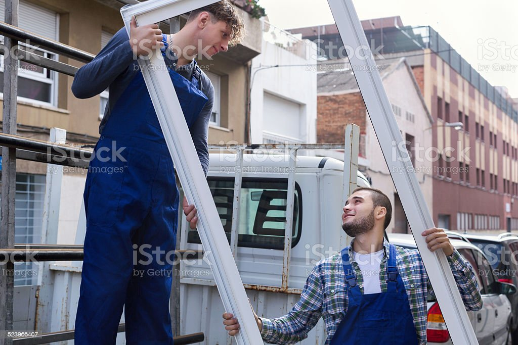 Two workers delivering PVC profiles stock photo
