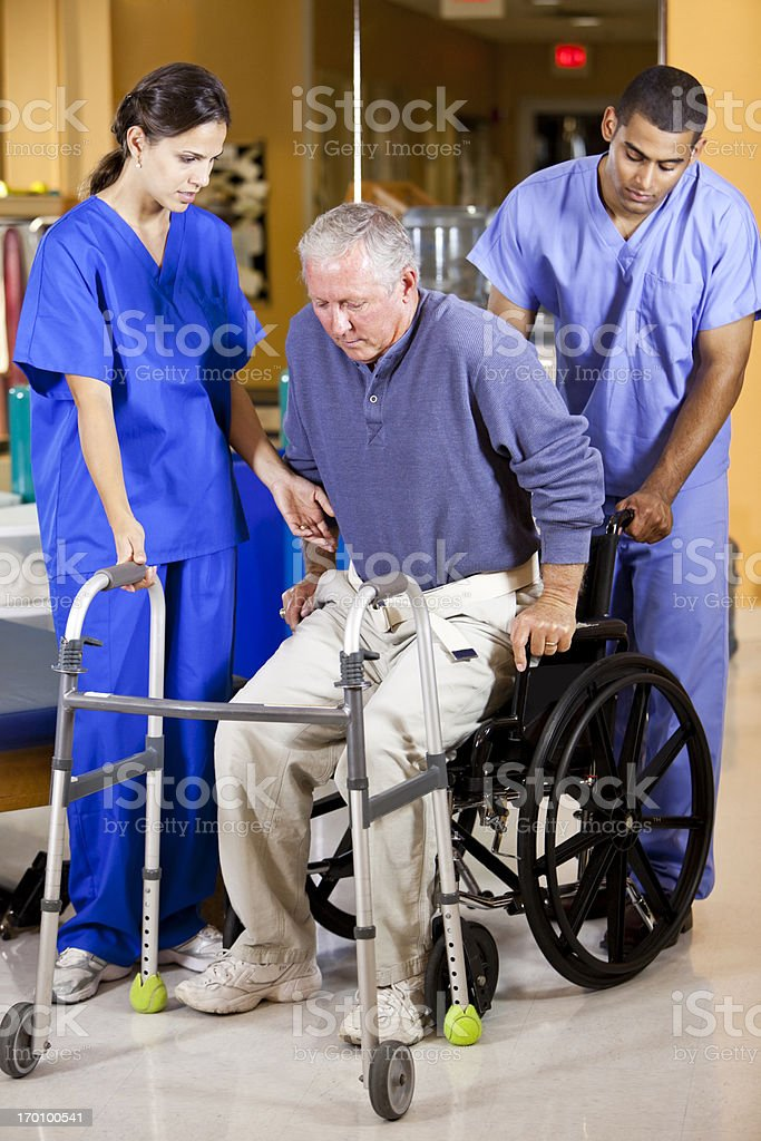 Two workers help man out of wheelchair onto walker stock photo
