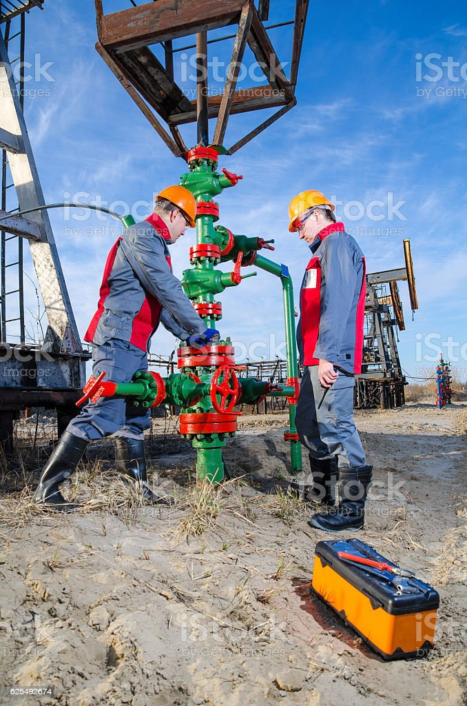 Two workers in the oilfield stock photo