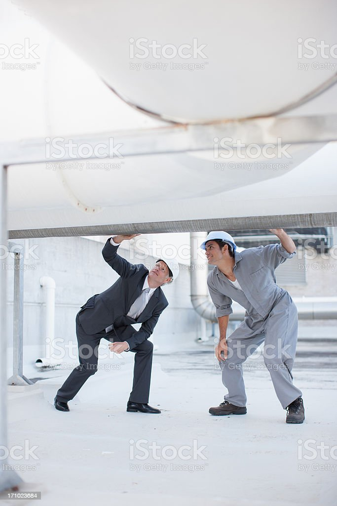 Two workers inspecting pipe stock photo