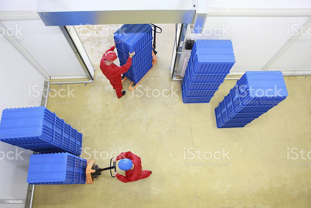 two workers loading plastic boxes in small warehouse royalty-free stock photo