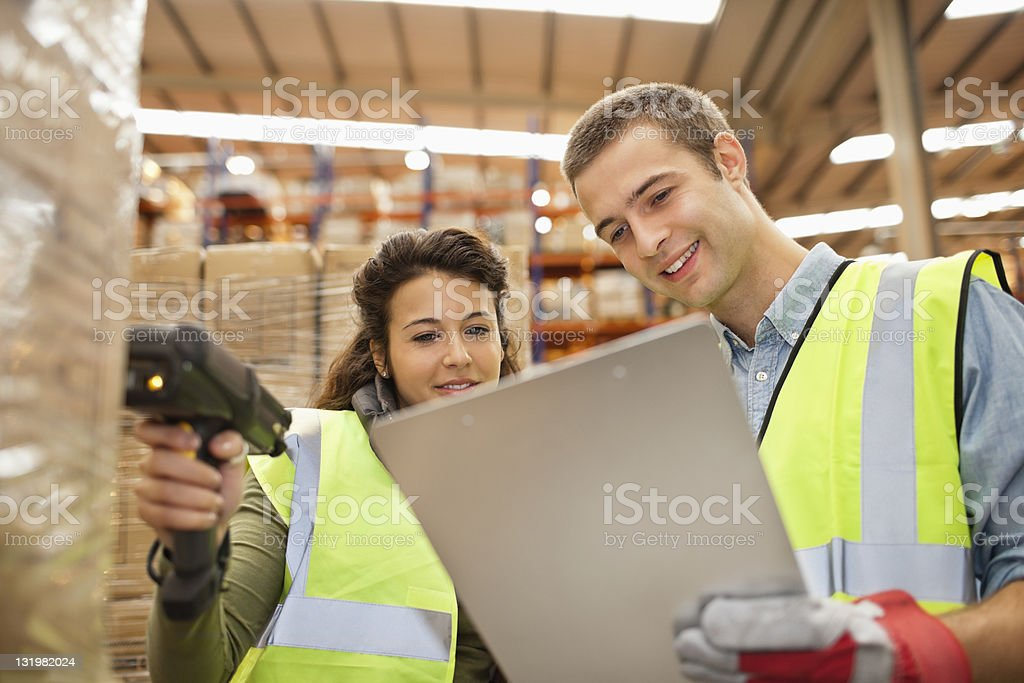 Two workers looking at checklist while scanning barcodes on cardboard boxes stock photo