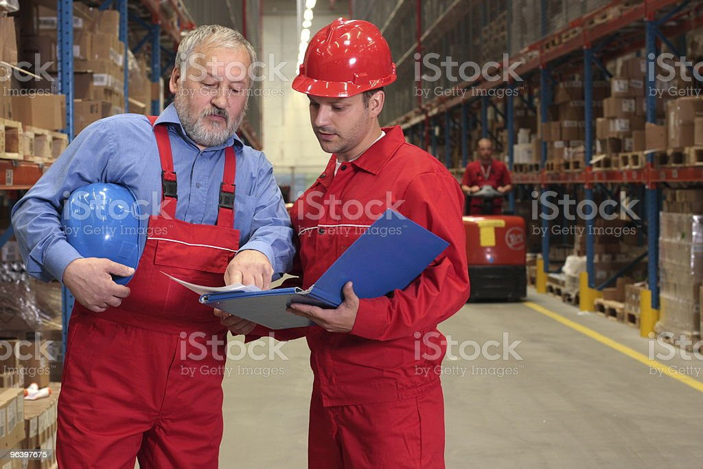 two workers  reviewing papers  in warehouse stock photo