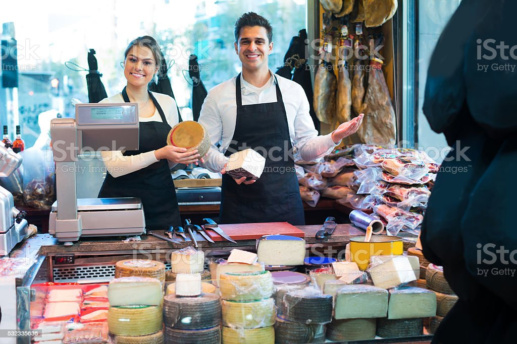 Two workers selling cheese and sausages stock photo