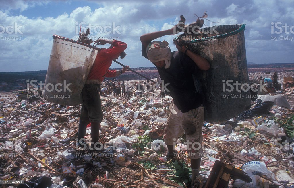 Two workers sifting through litter at a landfill stock photo