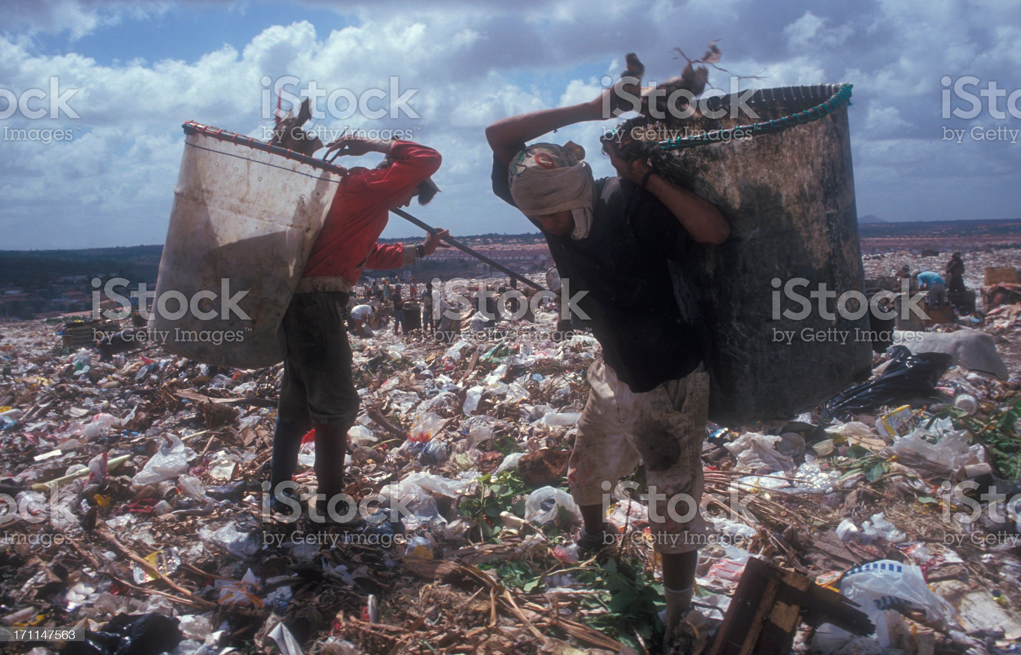 Two workers sifting through litter at a landfill royalty-free stock photo