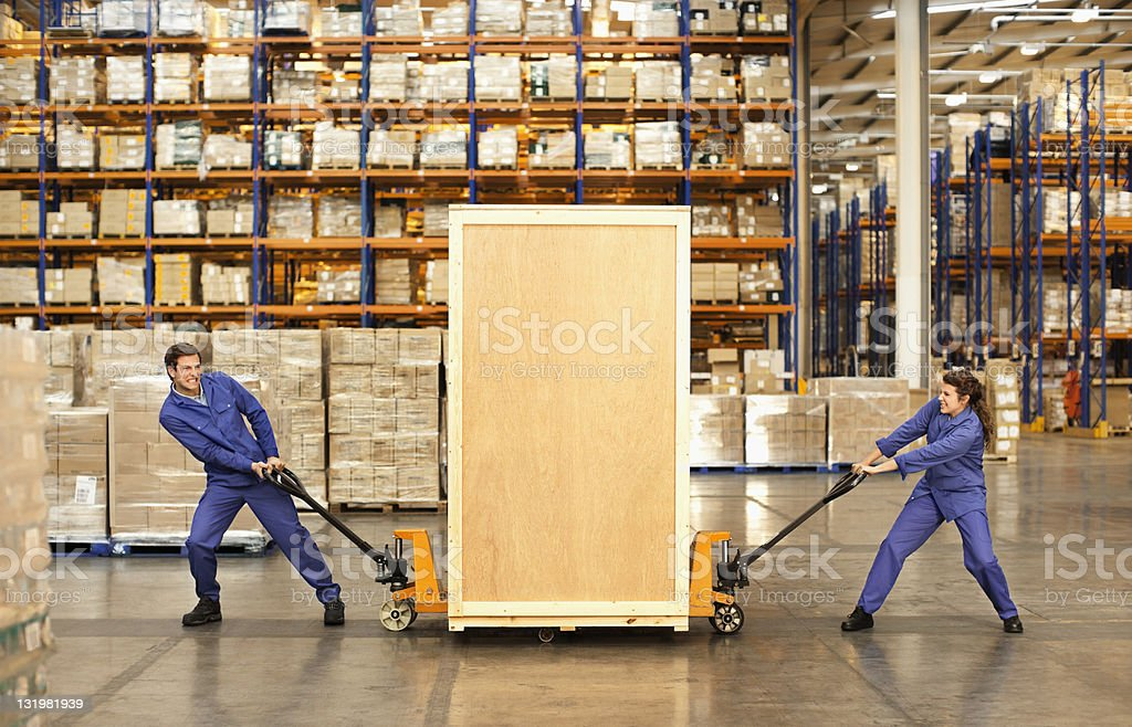 Two workers trying to pull heavy load of box through warehouse stock photo
