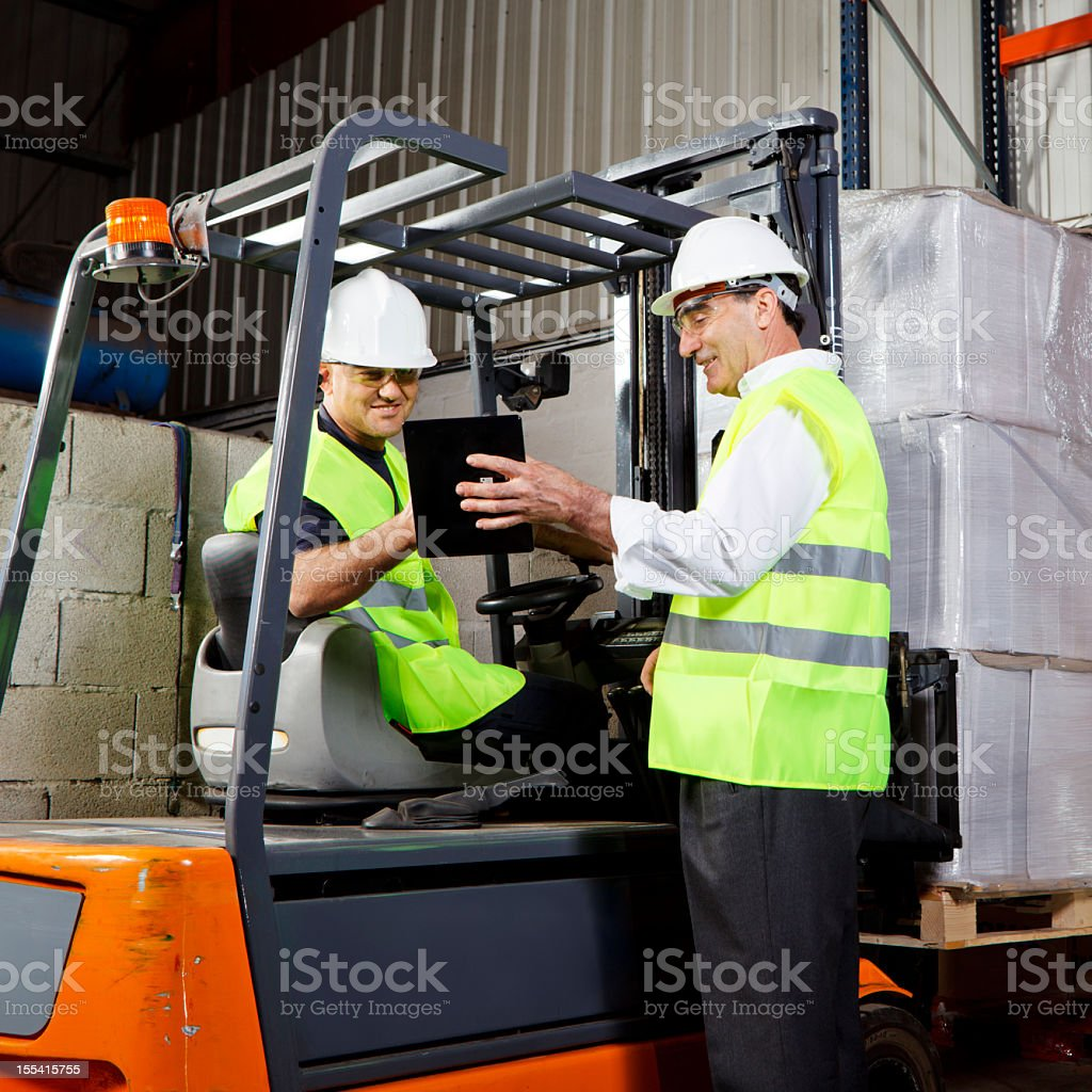 Two workers wearing hard hats with a tablet in a warehouse royalty-free stock photo
