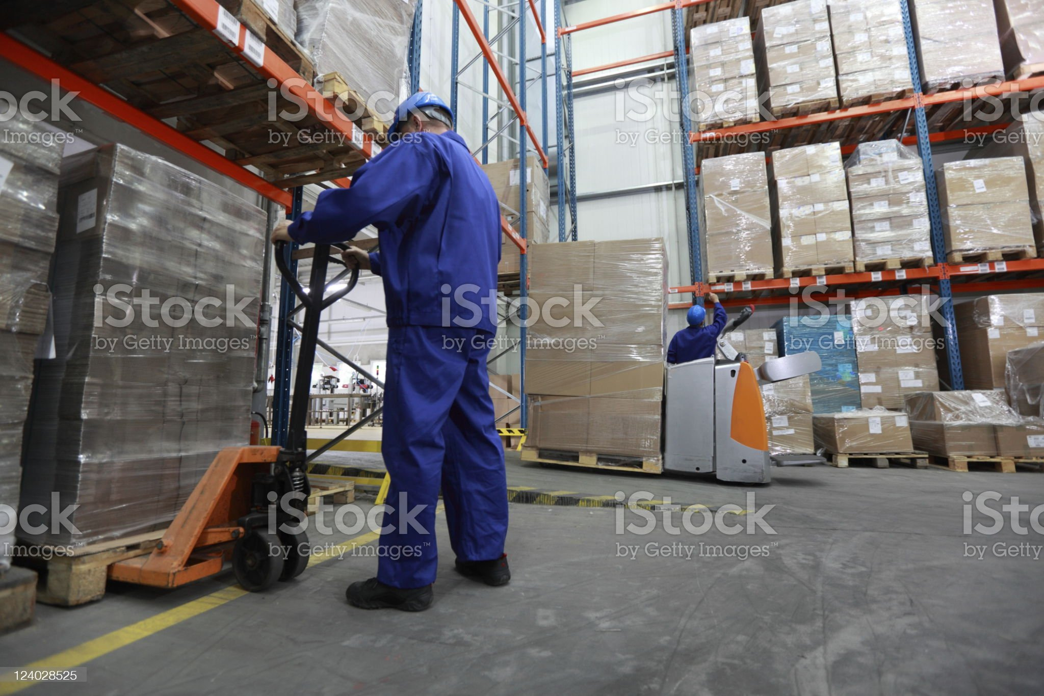 Two workers working in storehouse moving huge boxes royalty-free stock photo