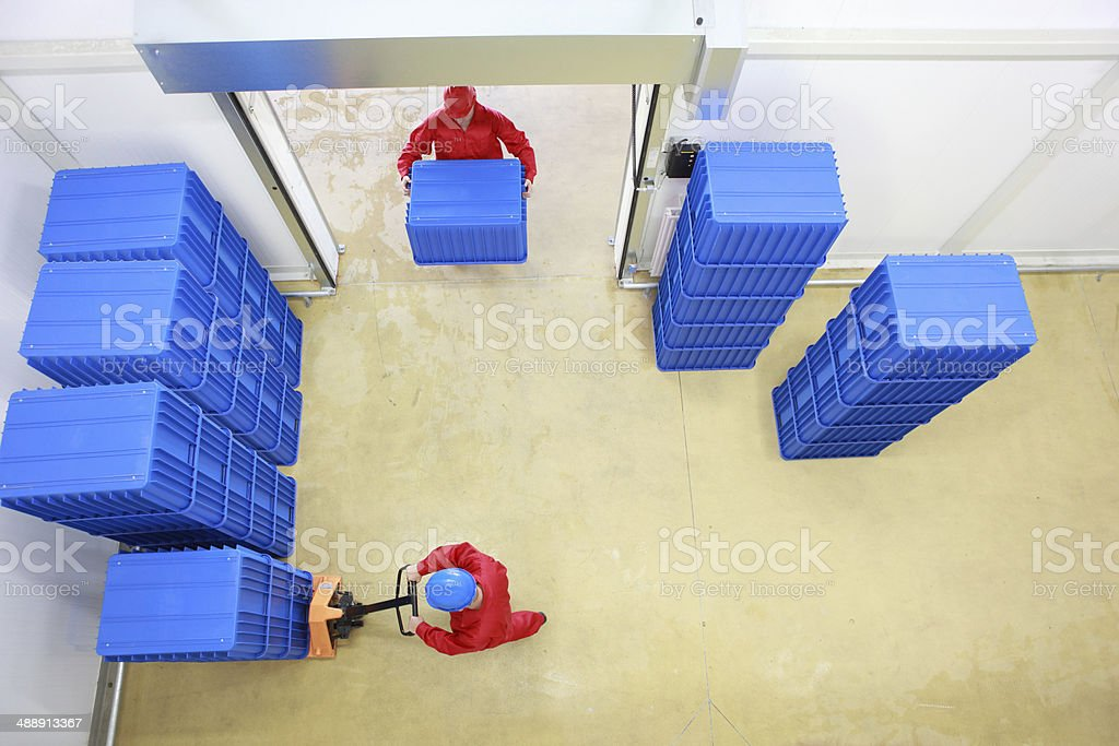 two workers working with plastic blue boxes in small warehouse stock photo