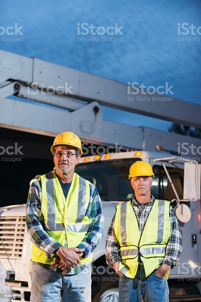 Two workmen in safety vests with truck stock photo