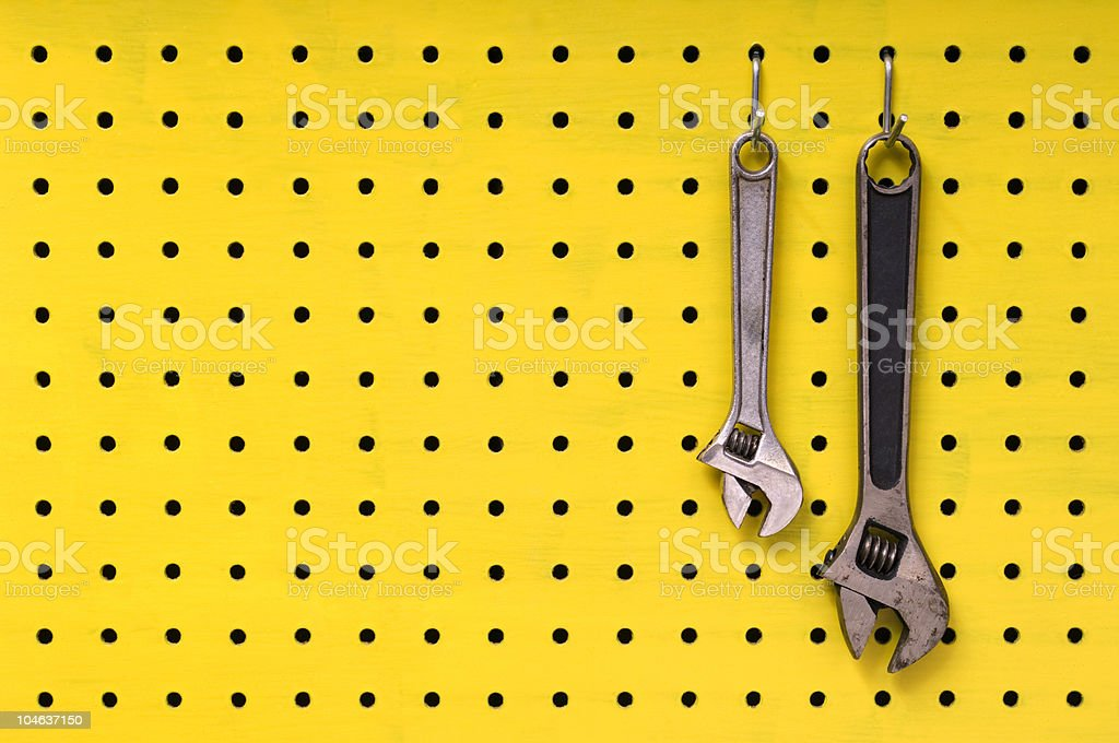 Two wrenches hang from hooks on yellow pegboard stock photo